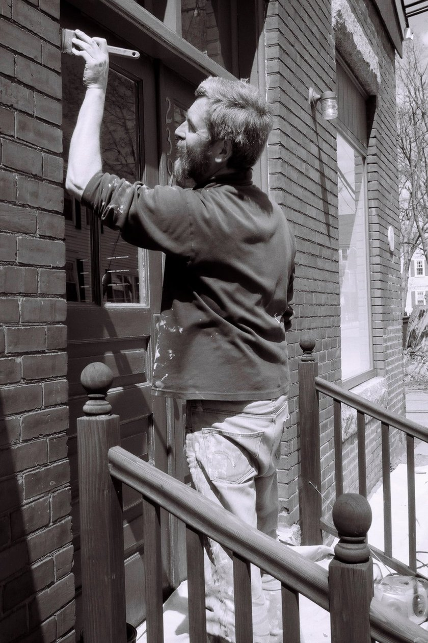 Local painter Davison Bolster touches up a historic building on Water Street. Photo credit LJ Henley.